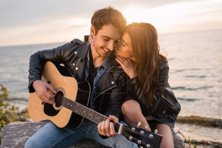Photo for Young woman kissing boyfriend playing acoustic guitar on seaside during sunset - Royalty Free Image