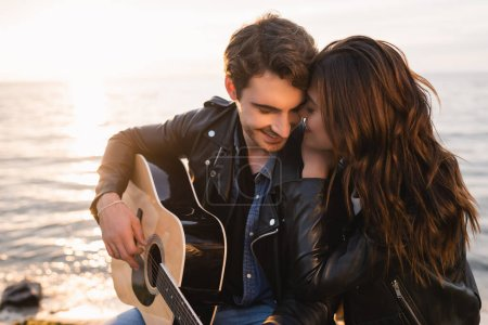 Photo for Woman embracing boyfriend playing acoustic guitar near sea on beach at evening - Royalty Free Image