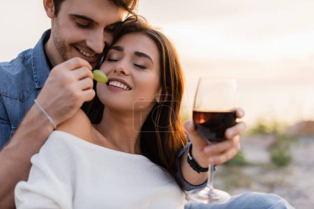 Photo for Selective focus of man feeding girlfriend with grape while holding glass of wine on beach - Royalty Free Image