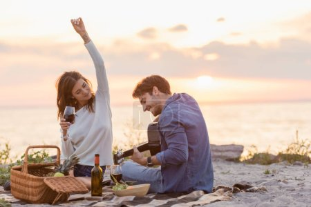 Selective focus of woman holding glass of wine near boyfriend playing acoustic guitar during picnic on beach