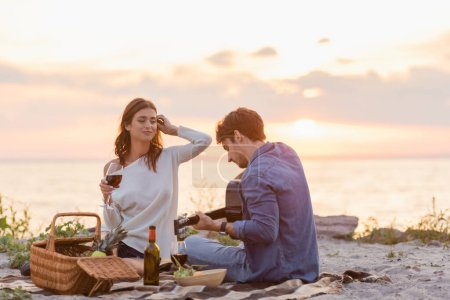 Photo for Couple playing acoustic guitar during picnic with wine on beach at sunset - Royalty Free Image