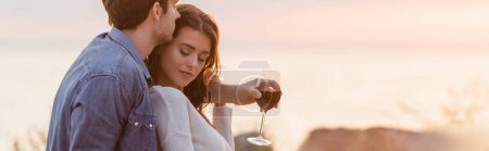 Photo for Website header of man hugging woman while holding glass of wine on beach at sunset - Royalty Free Image