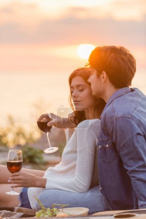 Selective focus of man embracing girlfriend with glass of wine near acoustic guitar on beach