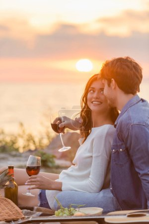 Selective focus of young couple holding glasses of wine near acoustic guitar