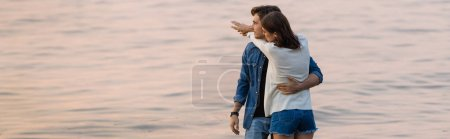 Photo for Horizontal image of young woman hugging boyfriend near sea at sunset - Royalty Free Image
