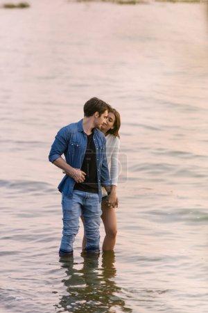 Photo pour Jeune couple tenant la main dans l'eau de mer au coucher du soleil - image libre de droit