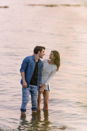 Photo pour Brunette femme toucher copain tandis que debout dans l'eau de mer au coucher du soleil - image libre de droit