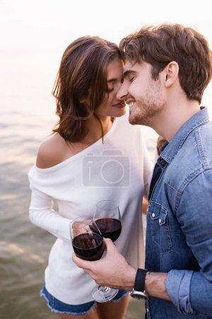 Photo pour Jeune homme avec un verre de vin debout près de la petite amie et la mer au coucher du soleil - image libre de droit