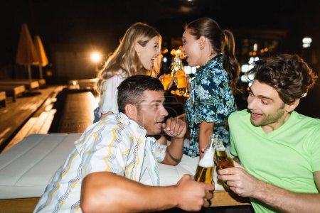 Photo for Selective focus of excited friends toasting with beer during party outdoors at night - Royalty Free Image