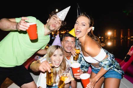 Selective focus of young friends in party caps holding beer bottles and disposable cups at night