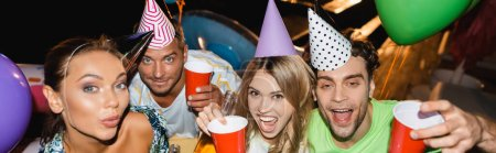 Photo for Panoramic orientation of excited friends in party caps holding disposable cups near balloons at night - Royalty Free Image