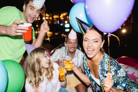 Selektiver Fokus der Frau mit Bierflasche und Luftballon bei nächtlicher Party mit Freunden