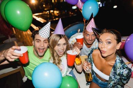 Photo pour Amis tenant des tasses jetables et des bouteilles de bière près des ballons pendant la fête la nuit - image libre de droit