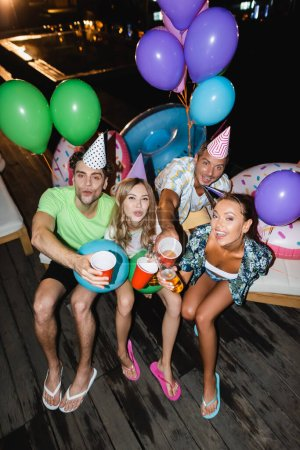 Young friends looking at camera while toasting with beer near balloons and swimming pool at night