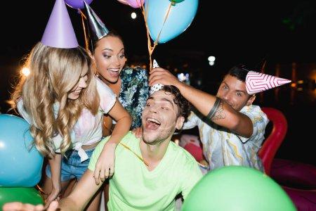 Photo pour Concentration sélective de l'homme portant une casquette de fête sur la tête d'un ami près des femmes et des ballons la nuit - image libre de droit