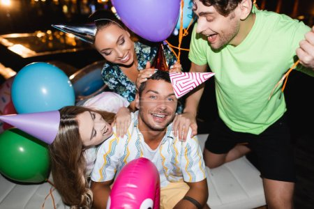 Photo for Selective focus of friends hugging young man in party cap near balloons and swimming pool at night - Royalty Free Image