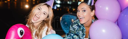 Website header of friends in party caps having fan with balloons at night