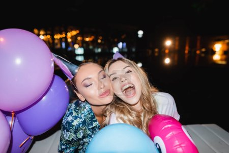 Selective focus of young women in party caps near balloons at night