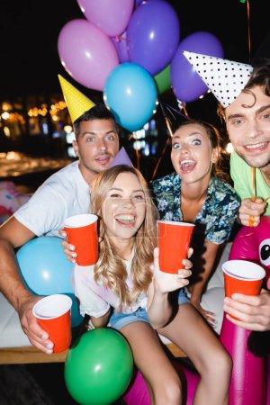 Photo pour Concentration sélective des amis tenant des tasses jetables pendant la fête avec des ballons la nuit - image libre de droit