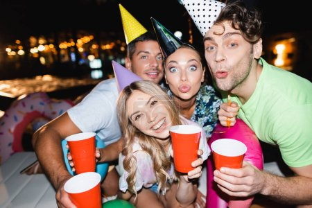 Selective focus of couples in party caps looking at camera while holding disposable cups at night