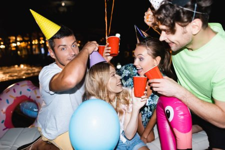 Selective focus of friends toasting with disposable cups near balloons during party at night