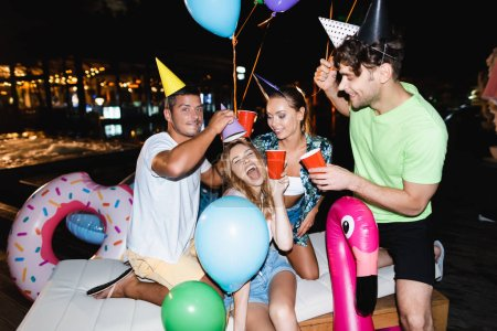 Photo for Friends in party caps holding disposable cups near swimming pool at night - Royalty Free Image