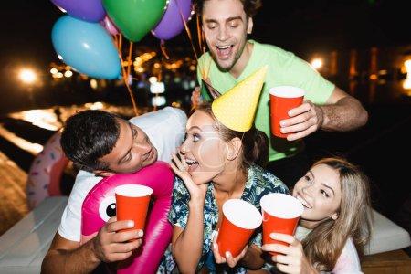 Selektiver Fokus der jungen Frau in Partymütze mit Einwegbecher in der Nähe von Freunden mit Luftballons in der Nacht