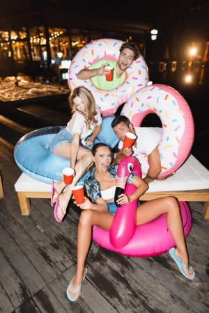 Friends holding disposable cups during party with swim rings near pool at night