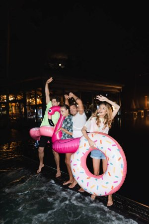 Friends dancing with swim rings during party near swimming pool at night