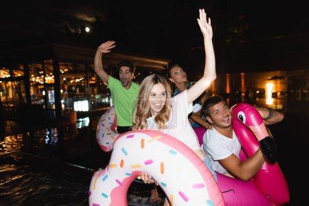 Photo pour Concentration sélective de la jeune femme tenant l'anneau de natation et agitant la main près des amis pendant la fête à la piscine la nuit - image libre de droit