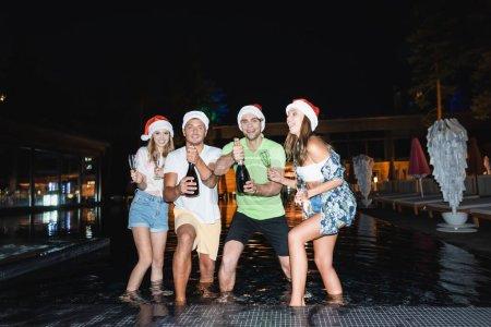 Photo pour Amis en chapeaux Santa tenant des verres et des bouteilles de champagne dans la piscine la nuit - image libre de droit