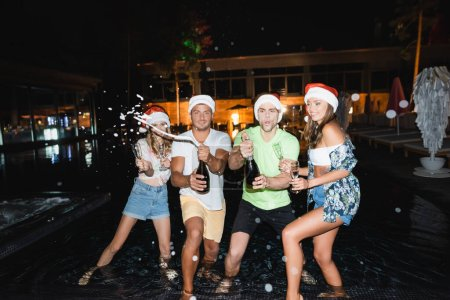 Photo for Selective focus of friends in santa hats opening champagne in swimming pool at night - Royalty Free Image