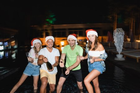Selective focus of young friends in santa hats holding glasses and bottles of champagne near swimming pool at night