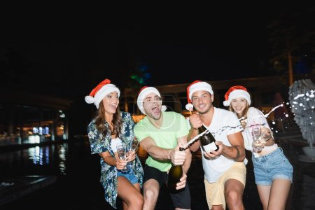 Selective focus of excited friends in santa hats opening champagne near pool at night