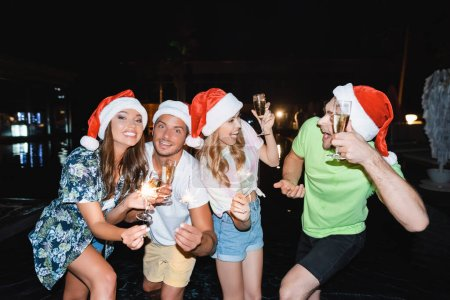 Friends in santa hats holding sparklers and champagne near swimming pool at night