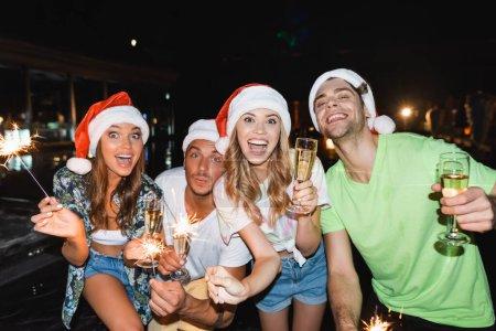 Photo pour Des amis excités dans des chapeaux de Père Noël avec des étincelles et du champagne regardant la caméra la nuit - image libre de droit