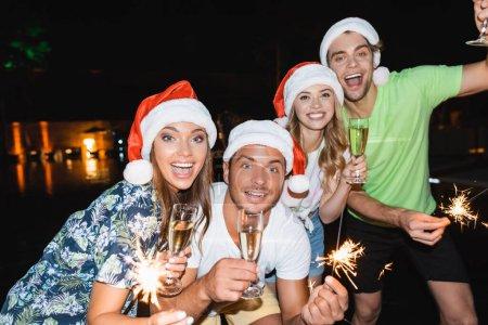 Photo pour Focus sélectif des jeunes célébrant le Nouvel An avec champagne et étincelles la nuit en plein air - image libre de droit