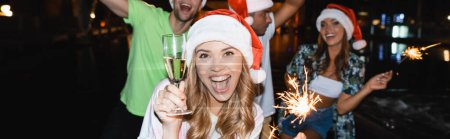 Photo for Horizontal image of excited woman holding glass of champagne and sparkler while celebrating new year at night outdoors - Royalty Free Image