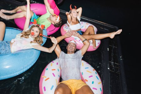 High angle view of young people in party headbands with blow ticklers swimming on rings in pool at night