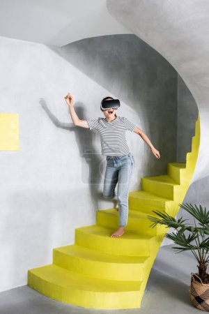 Photo for Woman in virtual reality headset going down stairs - Royalty Free Image