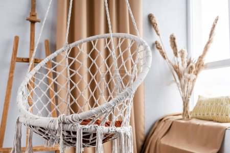 Photo for Modern studio interior with hanging chair and easel - Royalty Free Image