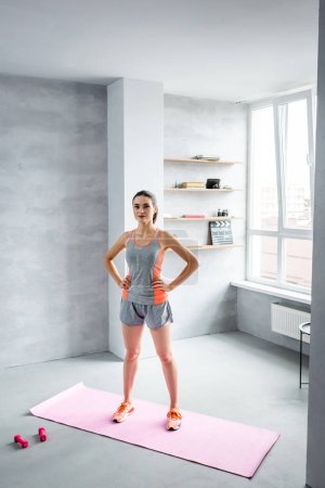Sportswoman standing with hands on hips on fitness mat near dumbbells at home