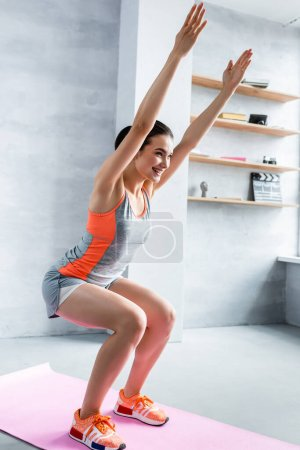 Photo for Young adult woman squatting with hands in air at home - Royalty Free Image