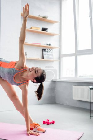 Sportswoman stretching on fitness mat near dumbbells at home