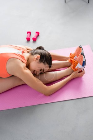 Photo pour Concentration sélective de la sportive étirant sur tapis de fitness près des haltères à la maison - image libre de droit