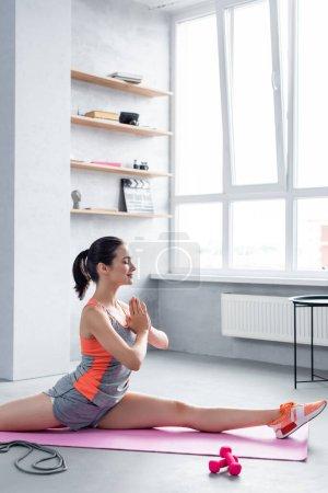 Photo pour Sportswoman avec des mains priantes faisant diviser sur tapis de fitness près de l'équipement sportif - image libre de droit