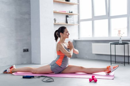 Photo for Sportswoman with praying hands stretching on fitness mat at home - Royalty Free Image