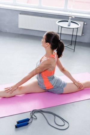 Photo pour Vue arrière de la sportive s'étirant sur un tapis de fitness près d'une corde à sauter à la maison - image libre de droit