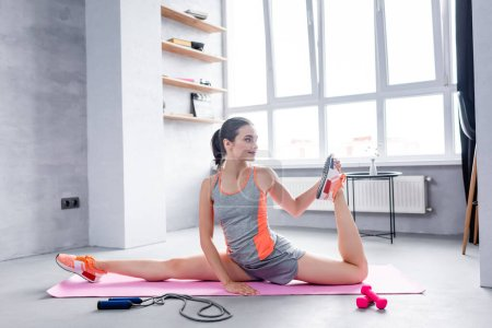 Sportswoman looking away and stretching on fitness mat near sport equipment