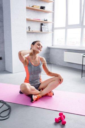 Photo pour Sportswoman assis avec les jambes croisées et étirement sur tapis de fitness à la maison - image libre de droit